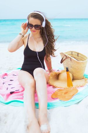 smiling modern 40 year old woman with long curly hair in elegant black swimsuit listening to the music with headphones while sitting on round watermelon towel on a white beach. 스톡 콘텐츠 - 130438335