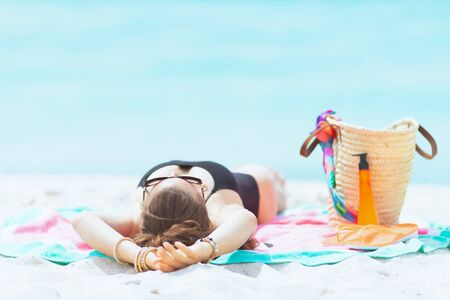 elegant middle age woman with long curly hair in elegant black swimsuit on a white beach sleeping while sun tanning.