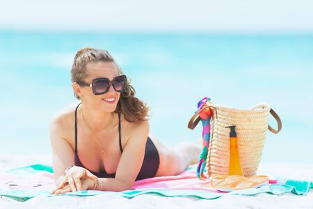 donna alla moda di 40 anni con lunghi capelli ricci in elegante costume da bagno nero su una spiaggia bianca che guarda lontano mentre si posa su un asciugamano rotondo di anguria.
