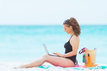 happy young 40 year old woman with long curly hair in elegant black swimsuit with laptop on a white beach. Banque d'images - 130438260