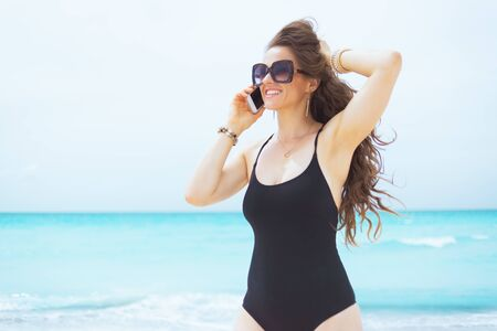 happy stylish 40 year old woman in sunglasses on a white beach speaking on a cell phone.