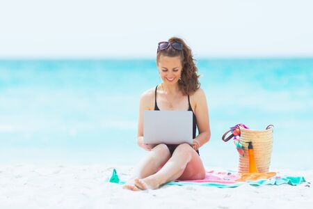 smiling stylish 40 year old woman with long curly hair in elegant black bathing suit with laptop on a white beach.
