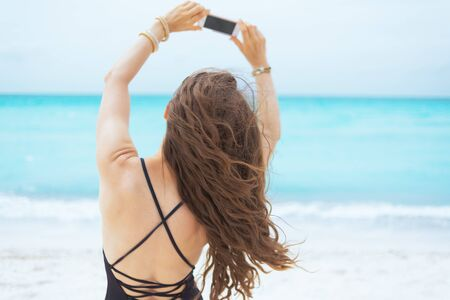 Seen from behind modern middle age woman with long curly hair in elegant black swimsuit taking photo with mobile phone on a white beach.