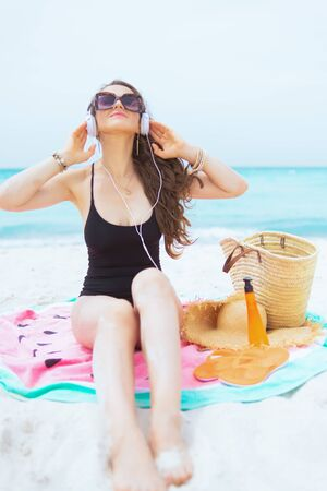 relaxed trendy 40 year old woman with long curly hair in elegant black bathing suit on a white beach relaxing while sitting on round watermelon towel.