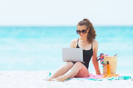 happy trendy middle age woman with long curly hair in elegant black swimsuit with laptop on a white beach.
