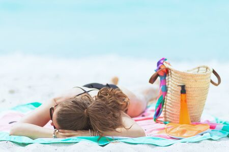 trendy 40 year old woman with long curly hair in elegant black bathing suit on a white beach sleeping while sun bathing.