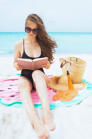 stylish 40 year old woman with long curly hair in elegant black swimsuit on a white beach reading book while sitting on round watermelon towel. 스톡 콘텐츠