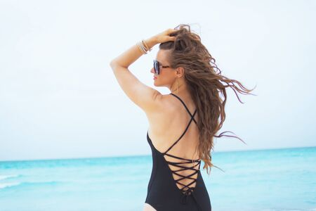 young middle age woman with long curly hair in elegant black swimsuit on a white beach relaxing.