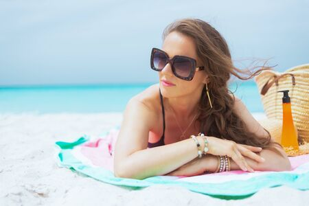 modern middle age woman in sunglasses and with long curly hair in elegant black bathing suit on a white beach looking into the distance and sun bathing.
