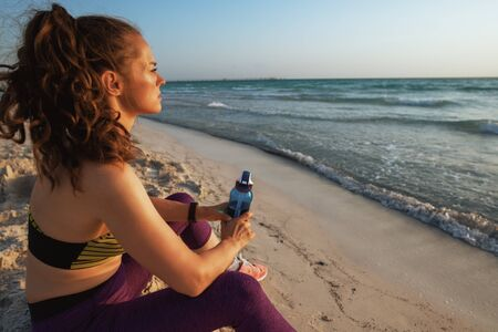 young sports woman in sport clothes with bottle of water looking into the distance while sitting on the seashore at sunset. 版權商用圖片