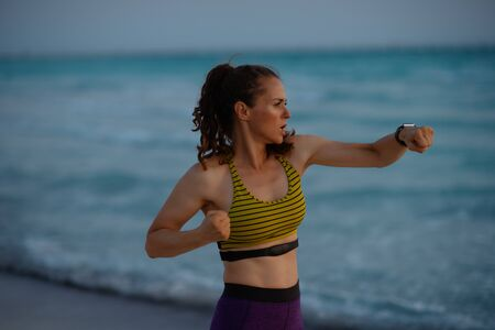 fitness sports woman in sport style clothes on the ocean shore in the evening boxing.