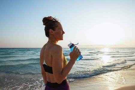 young woman in fitness clothes with bottle of water on the ocean coast at sunset.