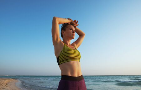 fit woman in sport clothes on the ocean shore in the evening looking into the distance.