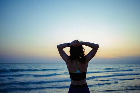 Seen from behind healthy sports woman in sport style clothes on the ocean shore in the evening looking into the distance and relaxing after workout.