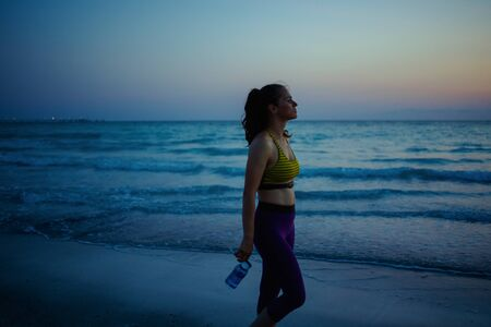 Silhouette of fitness sports woman in sport clothes with bottle of water relaxing after workout on the ocean shore in the evening.