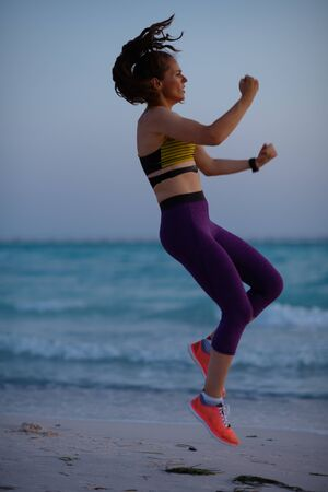 Full length portrait of young sports woman in sport clothes on the beach in the evening workout.