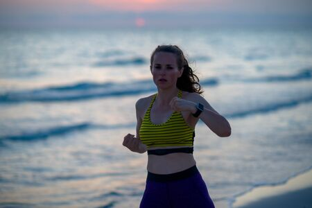 active woman in fitness clothes on the seashore in the evening boxing. 写真素材
