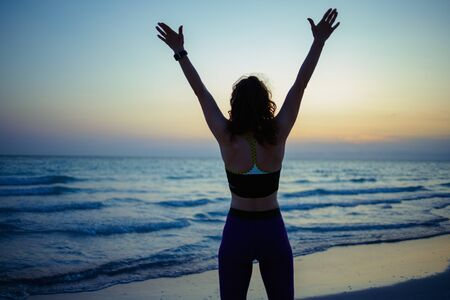 Seen from behind active woman in fitness clothes with open arms rejoicing on the seashore in the evening. 写真素材