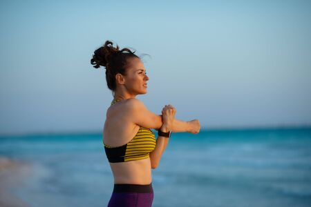 fitness sports woman in sport clothes on the ocean coast at sunset stretching.
