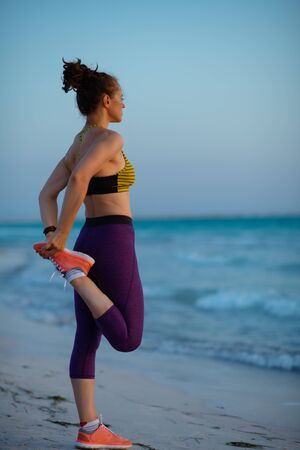 Full length portrait of healthy woman in fitness clothes on the ocean shore at sunset stretching. Stockfoto