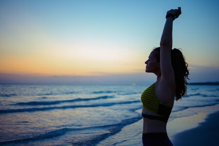 Silhouette of young sports woman in sport style clothes on the ocean coast in the evening stretching. Stockfoto