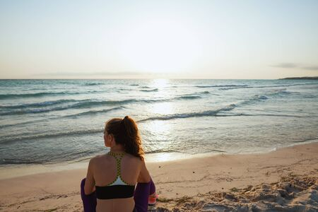 Seen from behind young sports woman in sport style clothes sitting on the seashore at sunset.