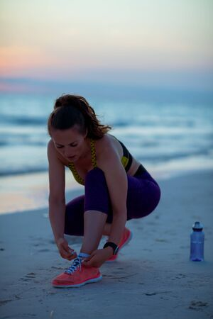 fitness woman in sport clothes on the seacoast in the evening tying shoelaces. 写真素材