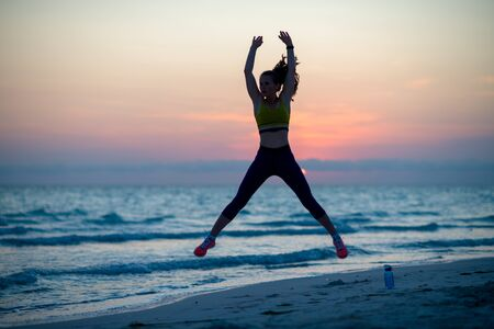 Silhouette of fitness woman in sport style clothes on the ocean coast in the evening workout.