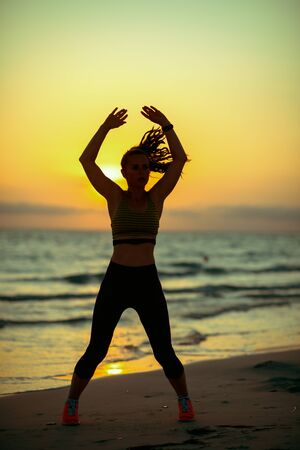Silhouette of fitness sports woman in sport clothes on the ocean coast at sunset training.