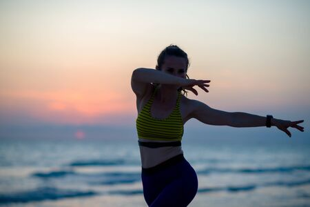 Silhouette of fitness sports woman in sport clothes on the ocean coast in the evening doing martial arts training.