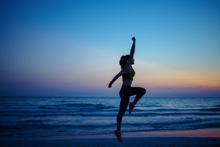 Silhouette of healthy sports woman in sport style clothes on the seashore in the evening training.