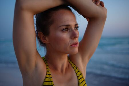 active sports woman in fitness clothes on the seashore in the evening relaxing after workout. 版權商用圖片
