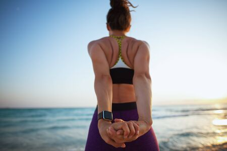 Seen from behind young sports woman in fitness clothes on the beach at sunset stretching.