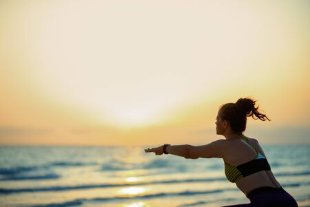 Silhouette of fit sports woman in sport clothes on the beach in the evening doing squats.