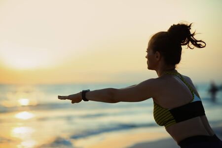 Silhouette of fit sports woman in sport clothes on the seacoast at sunset doing squats.