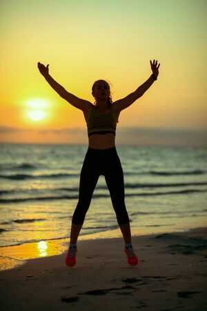 Silhouette of young sports woman in fitness clothes on the seashore in the evening training.