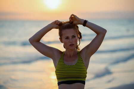 Portrait of healthy woman in sport style clothes on the seashore in the evening adjusting hair.