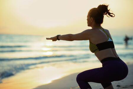 Silhouette of healthy woman in sport clothes on the seashore at sunset doing squats.