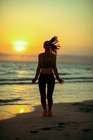 Silhouette of fitness sports woman in fitness clothes on the seacoast in the evening training.