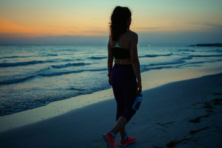 Seen from behind fitness sports woman in fitness clothes with bottle of water walking after workout on the ocean shore in the evening.