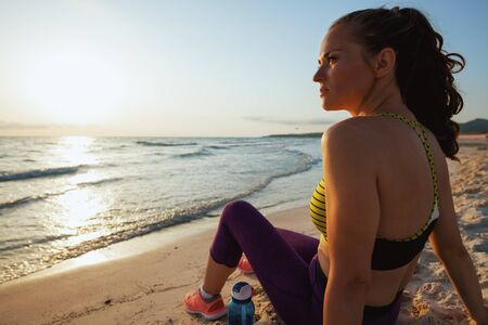 active sports woman in sport style clothes with bottle of water sitting and looking into the distance on the ocean shore in the evening. Standard-Bild