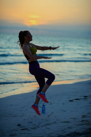 Silhouette of fitness sports woman in sport clothes on the ocean coast at sunset doing HIIT workout.