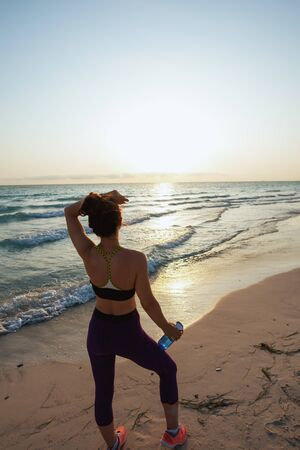 Seen from behind fit woman in sport clothes with bottle of water relaxing after workout on the ocean coast in the evening. Banco de Imagens