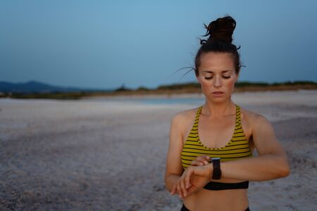 fitness sports woman in sport style clothes on the beach in the evening using smart watch to track weight in fitness app. Stock Photo