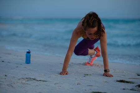 healthy sports woman in sport style clothes on the ocean coast in the evening workout.