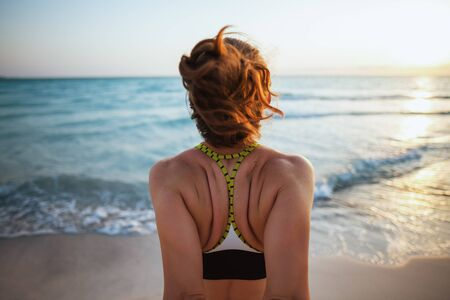 Seen from behind healthy sports woman in sport style clothes on the ocean shore at sunset stretching.