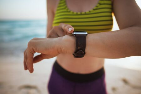 Closeup on fit woman in sport style clothes on the seacoast at sunset with smart watch using app to track fitness activity.