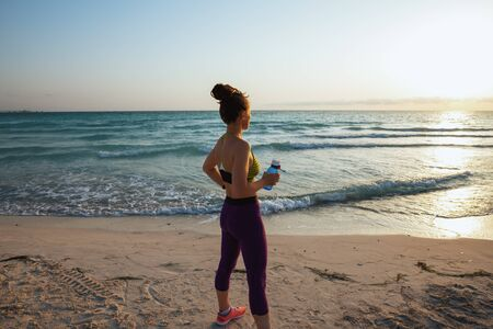 Seen from behind healthy woman in fitness clothes with water bottle looking into the distance on the ocean shore in the evening.