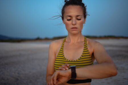 Portrait of fit sports woman in sport clothes on the seashore at sunset using smart watch to track steps, runs or rides in fitness app.