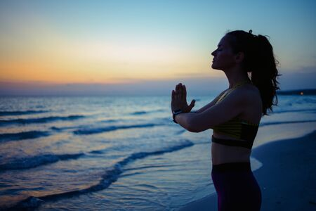 Silhouette of young woman in fitness clothes on the ocean shore in the evening meditating. Imagens
